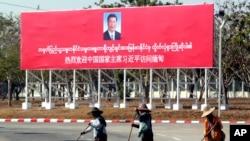 រូបឯកសារ៖ អ្នកបោសសម្អាតនៅខាងមុខផ្ទាំងស្វាគមន៍ប្រធានាធិបតីចិនលោក Xi Jinping កាលពីថ្ងៃទី១៧ ខែមករា ឆ្នាំ២០២០។