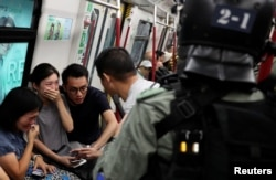 Commuters react as police officers looking for protestors raid a metro train, in Hong Kong, China September 1, 2019.