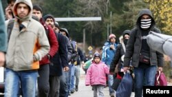 FILE - Migrants walk along a street after passing the Austrian-German border near Wegscheid, Germany, Nov. 12, 2015.