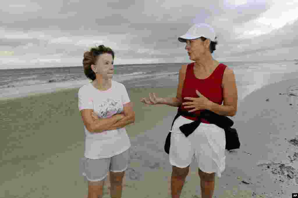 Charlotte Timmons, 63, and Brenda Batey, 60, discuss their concerns about community preparations for Tropical Storm Isaac during their morning walk along the beach in west Gulfport, Miss., Aug. 28, 2012.