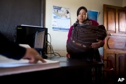 Maria Micaela Panjoc puts in a request for alimony payments to help her with the costs of raising her son, at the Indigenous City Hall in Solola, Guatemala, Jan. 16, 2017 photo.