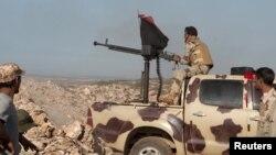 Des membres des forces pro-gouvernementales libyennes visent une arme lors de leur déploiement dans la zone de Lamluda, au sud-ouest de Derna, le 16 juin 2015 (REUTERS).