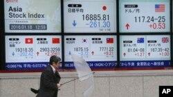 Seorang pria melewati papan informasi saham elektronik di depan sebuah perusahaan sekuritas di Tokyo (18/1).