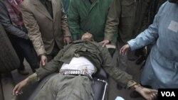 Meédicos y voluntarios evacuan a un combatiente opositor muerto tras los bombardeos de las tropas de Gadhafi en Ras Lanouf.