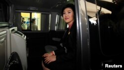 Ousted former Prime Minister Yingluck Shinawatra sits in her car as she leaves Parliament after delivering her statement to the National Legislative Assembly meeting in Bangkok, January 9, 2015.