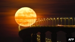 "The French ""lunatique"" means insane. Many ancient cultures blame the moon for insanity. Here, a full moon rising over the Re Island Bridge in Rivedoux, France."