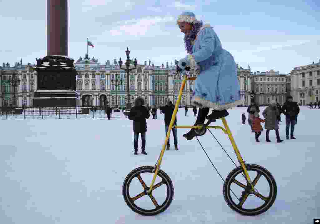 A woman wearing a Snow Maiden costume rides a bike during celebration Old New Year at Dvortsovaya (Palace) Square in St.Petersburg, Russia.