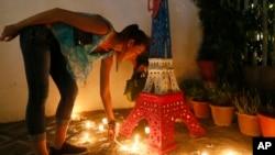 Une française allume des bougies devant une réplique Tour Eiffel à l'extérieur de l'Alliance Français en mémoire des victimes des attaques de Paris, lundi 16 novembre 2015 au quartier financier de Makati City, à l'est de Manille, Philippines.