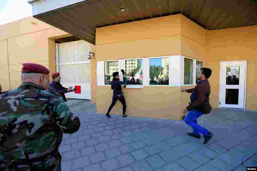 Un manifestante ataca con su zapato una de las ventanas de la embajada de Estados Unidos durante una protesta para mostrar su rechazo a los ataques de Washington en los que murieron 25 combatientes (Foto: Reuters/Thaier al-Sudani)