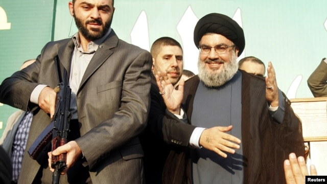 Lebanon's Hezbollah leader Sayyed Hassan Nasrallah (R), escorted by his bodyguards, makes a rare public appearance as he greets his supporters at an anti-U.S. protest in Beirut's southern suburbs September 17, 2012.