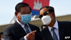 FILE- Cambodia's Minister of Interior Sar Kheng (L) and Prime Minister Hun Sen (R) talk during King Norodom Sihamoni's departure to China for a health check-up at Phnom Penh International Airport in Phnom Penh on October 6, 2020. (Photo by TANG CHHIN Sothy / AFP)