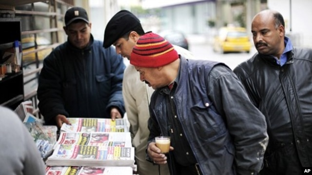 Men look at newspapers at a street kiosk in downtown Tunis, 19 Jan 2011
