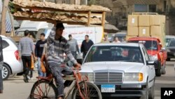 In this March 16, 2013 photo, an Egyptian bread vendor rides his bicycle in downtown Cairo.