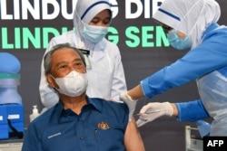Perdana Menteri Malaysia Muhyiddin Yassin menerima dosis pertama vaksin COVID-19 produksi Pfizer / BioNTech, di sebuah klinik pemerintah di Putrajaya, 24 Februari 2021. (Foto: AFP PHOTO / MALAYSIA'S DEPARTMENT OF INFORMATION)
