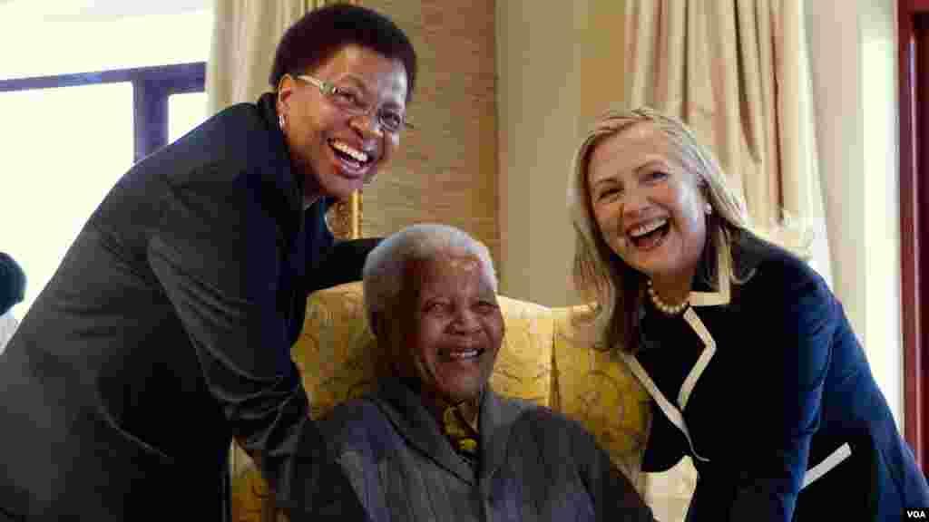 Nelson Mandela, 94, ancien président de l'Afrique du Sud, au centre et son épouse Graça Machel, à gauche, pose pour une photo avec la Secrétaire d'Etat américaine Hillary Clinton, à droite, à Qunu, Afrique du Sud, le 6 août 2012.