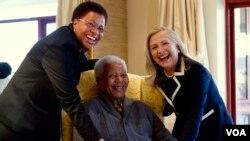 L'ancienne Secrétaire d'Etat américaine Hillary Clinton (R) pose pour une photo avec Nelson Mandela, 94, ancien président de l'Afrique du Sud, et son épouse Graça Machel (L) à son domicile de Qunu, Afrique du Sud, le 6 Août 2012.