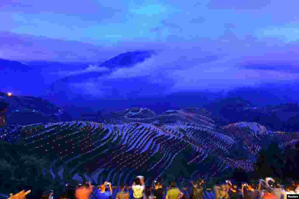 មនុស្សម្នាថតរូបពិលរាប់ពាន់ដែលគេបំពាក់នៅតាមជំរាលភ្នំ ក្នុងពិធីក្នុងស្រុកមួយ ដើម្បីបួងសួងសុំឲ្យទទួលផលកសិកម្មល្អ នៅក្នុងក្រុង Guilin តំបន់ Guangxi Zhuang ប្រទេសចិន។