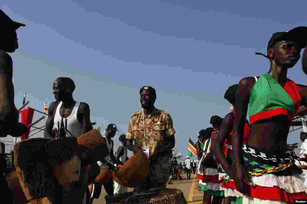 A Sudan People's Liberation Army (SPLA) soldier sings next to traditional dancers during celebrations marking the third anniversary of South Sudan's independence in Juba, July 9, 2014.