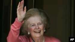 Former British Prime Minister Margaret Thatcher, gestures to members of the media as she stands on her house doorstep, following her return home from hospital, in central London, June 29, 2009.