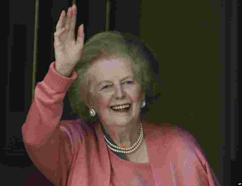 Former British Prime Minister Margaret Thatcher gestures to members of the media as she stands on her house doorstep, following her return home from hospital, in central London, June 29, 2009.