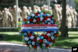 NATO forces stand behind a wreath during a memorial ceremony on the fourteenth anniversary of the 9/11 terrorist attacks on the United States at the headquarters of the International Security Assistance Force, in Kabul, Afghanistan, Sept. 11, 2015.