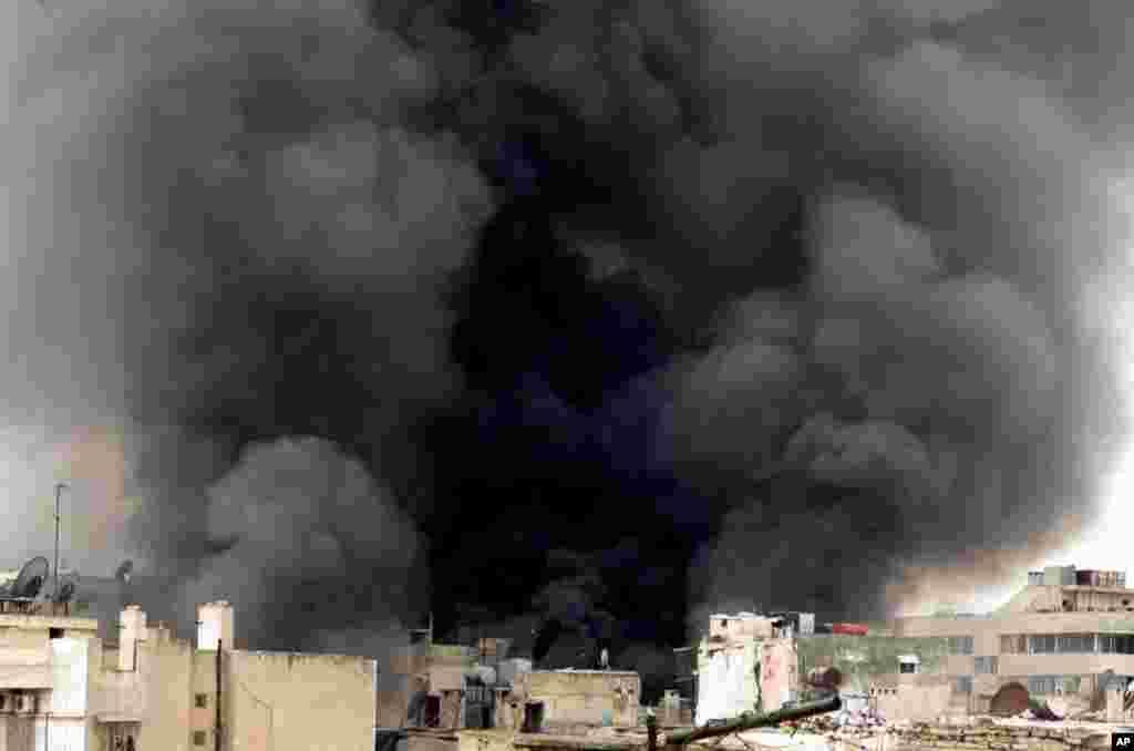 2013年3月19日叙利亚阿勒颇的楼房被政府军的炮火击中,冒起熊熊黑烟。