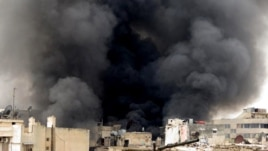 A citizen journalism image provided by Aleppo Media Center, which has been authenticated based on its contents and other AP reporting, shows black smoke rising from buildings due to government forces shelling, in Aleppo, Syria, March 19, 2013.