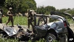Tentara AS memeriksa mobil yang hancur akibat bom pinggir jalan di distrik Khugyani, provinsi Jalalabad di Afghanistan (21/7).