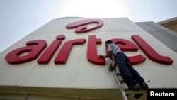 FILE - A worker cleans a logo of Bharti Airtel at its zonal office building in the northern Indian city of Chandigarh.
