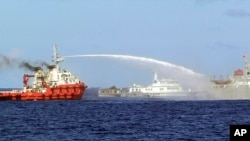 FILE - In this photo released by Vietnam Coast Guard, a Chinese ship (L) shoots a water cannon at a Vietnamese vessel (R) while a Chinese Coast Guard ship (C) sails alongside in the South China Sea, off Vietnam's coast, May 7, 2014.