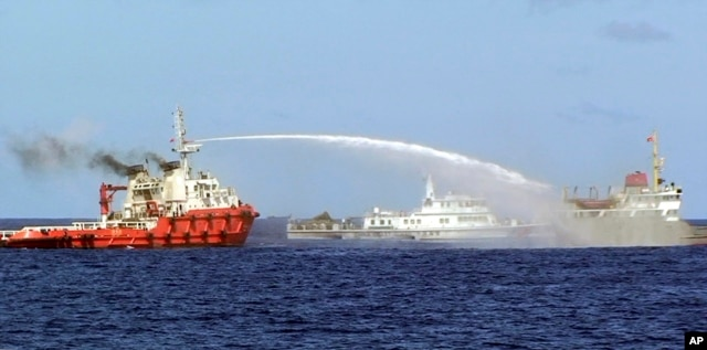 In this photo released by Vietnam Coast Guard, a Chinese ship (L) shoots a water cannon at a Vietnamese vessel (R) while a Chinese Coast Guard ship (C) sails alongside in the South China Sea, off Vietnam's coast, May 7, 2014.