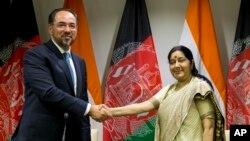 Menlu Afghanistan Salahuddin Rabbani (kiri) berjabat tangan dengan Menlu India Sushma Swaraj usai penandatanganan kesepakatan di New Delhi, India 11 September lalu (foto: dok).