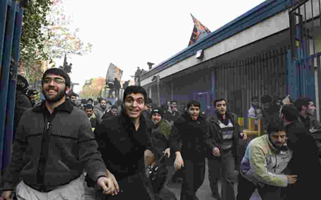 Los manifestantes cruzando la entrada de la embajada británica en Teherán, Irán.