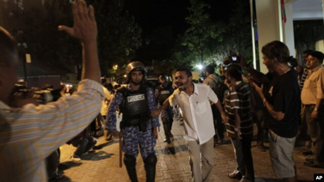 Supporters of Maldives' former President Mohamed Nasheed taunt a police officer during a protest in Male, Maldives, Sunday, Feb. 12, 2012.