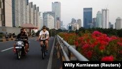 Seorang pria bermasker mengayuh sepeda melalui jalan utama saat pelonggaran PPKM di tengah pandemi COVID-19, di Jakarta, 28 Juli 2021. (Foto: REUTERS/Willy Kurniawan)