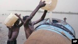 Des enfants soudanais remplissent un réservoir d'eau du fleuve Nil à Khartoum, au Soudan, 5 mai 2009.