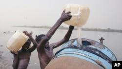 Des enfants soudanais remplissent un réservoir d'eau du fleuve Nil à Khartoum, au Soudan, 5 mai 2009. (AP Photo / Abd Raouf)