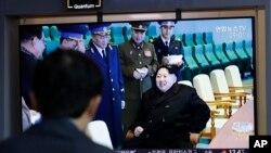 """一名男子在韩国首尔火车站观看朝鲜试射""""新型战术制导武器""""的电视新闻,其中包括朝鲜领导人金正恩的镜头(2019年4月18日)。"""