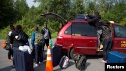 Une famille de réfugiés haitiens sortant leur bagage d'un taxi à leur arrivée à la frontière Etats unis-Canada, New York USA le 3 aout 2017. REUTERS/Christinne Muschi - RTS1A9NJ