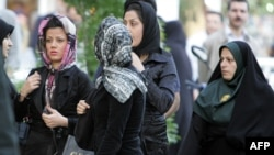 FILE - An Iranian policewoman (R) warns women about their clothing and hair during a crackdown to enforce Islamic dress code in Tehran, April 23, 2007.