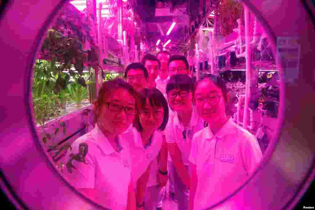 អ្នកស្ម័គ្រចិត្តញញឹមពីបន្ទប់មួយដែលពួកគេរស់នៅជាបណ្តោះអាសន្ន។ នេះជាផ្នែកមួយនៃគម្រោងវិទ្យាសាស្ត្រ Lunar Palace 365 នៅសាកលវិទ្យាល័យ Beihang ក្នុងក្រុងប៉េកាំង ប្រទេសចិន។