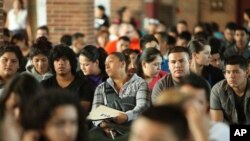 Undocumented people wait to fill out application forms for the Deferred Action for Childhood Arrivals program on August 15, 2012 at Navy Pier in Chicago, Illinois.