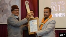 "FILE - Nepali Co-operatives and Poverty Alleviation Minister, Chitra Bahadur, left, hands the ""Integrity Idol"" trophy to civil servant and district administrator, Pradip Raj Kandel during an awards ceremony in Kathmandu, Jan. 10, 2016."