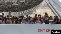 Migrants arrive on the British vessel HMS Enterprise before disembarking in the Sicilian harbor of Catania, Italy, Oct. 6, 2015. The Italian coastguard said on Tuesday some 1830 migrants were rescued from the Mediterranean sea in a twenty-four hour period
