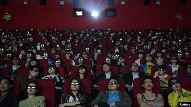 Espectadores ven un filme con espejuelos tridimensionales en una sala de cine en China.