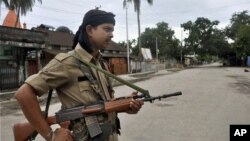 FILE - An Indian armed security man stands guard in Kokrajhar, India, July 24, 2012. Authorities say 15 people were wounded in the attack Friday in Kokrajhar, 220 kilometers west of the state commercial capital, Guwahati.
