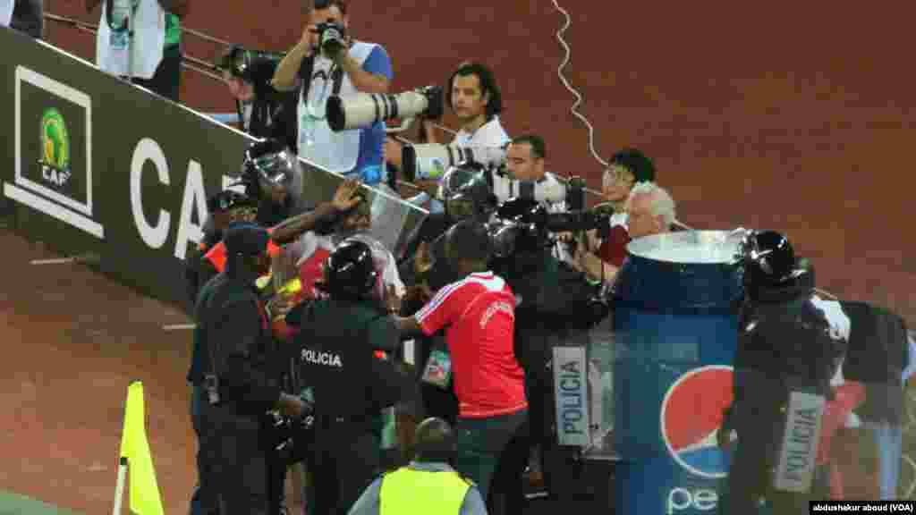 Policiais tentam remover torcedores da Guiné Equatorial que entraram no campo para comemorar após o país marcar um gol contra a Tunísia.