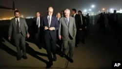 Secretary of State Rex Tillerson, right, walks on the tarmac as he arrives at Baghdad International Airport, Oct. 23, 2017, in Baghdad, Iraq.