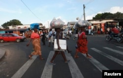 FILE - People cross a road in Monrovia.