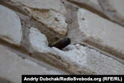 Куля від кулемета великого калібру ДШК, що нещодавно прилетіла у стіну будинку. Тома у той час гуляла на подвір'ї і бачила це